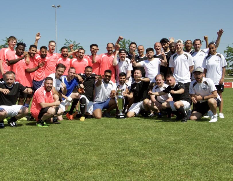 Verschiedene Fußballer in roten, schwarzen und weißen Trikos. Sarmi ist ganz rechts im Bild zu sehen. Sie ist die einzige weibliche Spielerin.