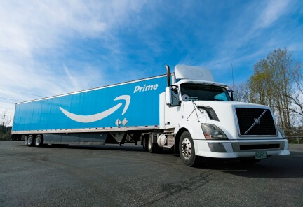 An Amazon Prime truck is showing against a blue sky.