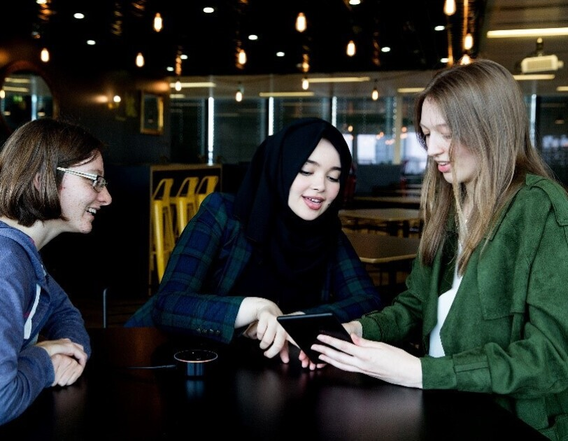 Three female students sat at a table smiling, talking and looking at a Kindle