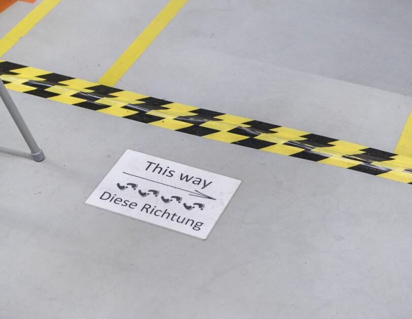 """Auf dem Boden einer Lagerhalle wurde ein Schild mit der Aufschrift """"This way - diese Richtung"""" angebracht."""