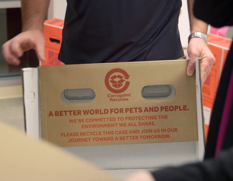 "A panel of a cardboard box marked with the words ""A better world for pets and people. We're committed to protecting the environment we all share. Please recycle this case and join us in our journey toward a better tomorrow."""