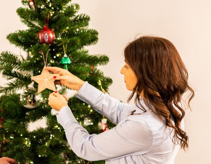 Marta y su familia se trasladaron de Londres a Madrid hace año y medio.  Marta colocando una estrella de cartón en el árbol de Navidad. Ella va con las uñas pintadas de rojo, lleva una camisa blanca y el pelo castaño largo.  el árbil de Navidad es de plástico y tienes decoraciones rojas, azules y bolas transparentes.