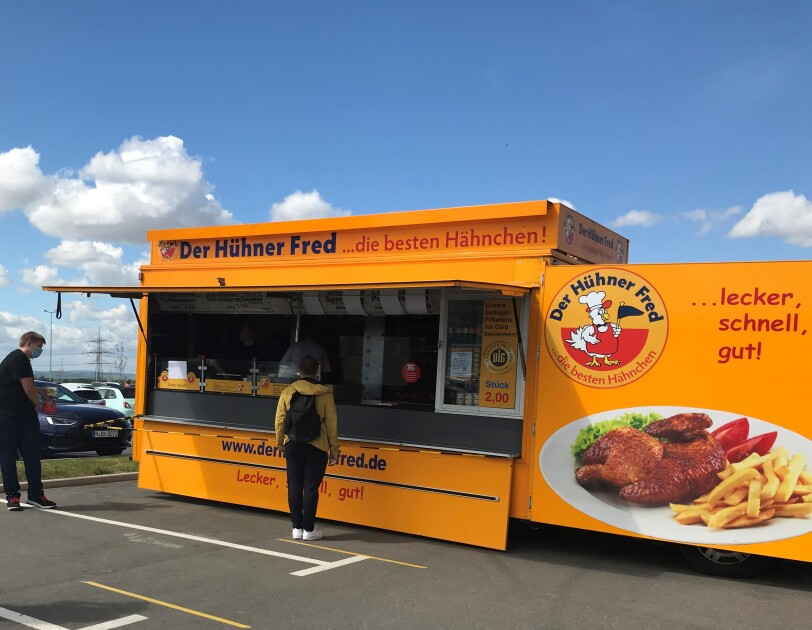 Ein gelber Food Truck mit Hühnerspeisen.