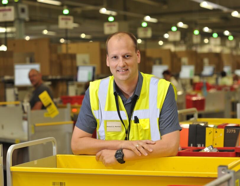 Robert Marhan in gelber Sicherheitsweise: Er stützt sich auf einen gelben Transportbehälter