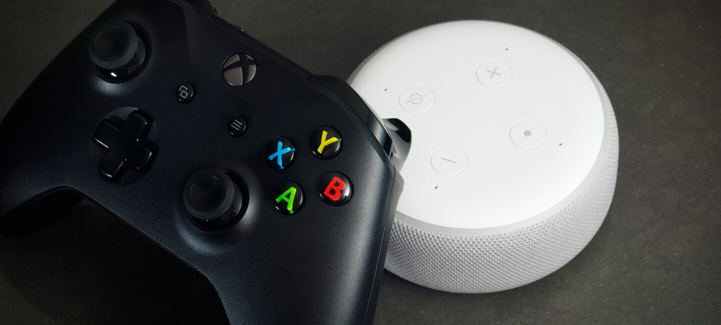 A black, wireless Xbox controller rests on a white Amazon Echo Dot. The background is gray.