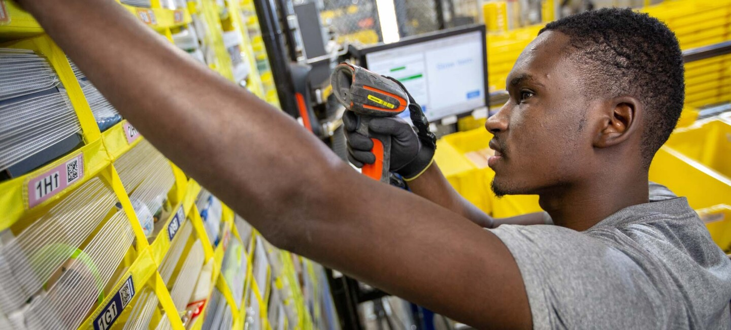 An Amazon associate holds a scanner in his left hand while reaching for a customer's product, at a Columbus, Ohio fulfillment center, CMH1