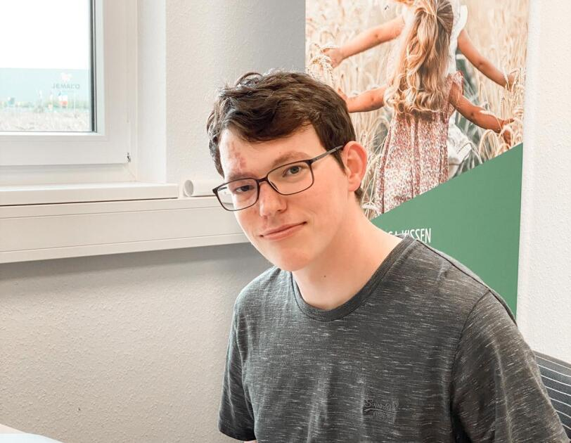 Ein Mann mit grauem T-shirt sitzt vor einem Computer und lächelt in die Kamera.