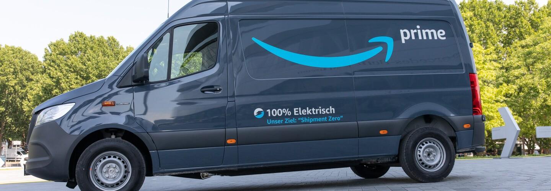 Una furgoneta eléctrica de Mercedes-Benz con el logo Prime de amazon y debajo en alemán 100% eléctrica. La furgoneta sin conductor está en una plaza con árboles en el fondo.