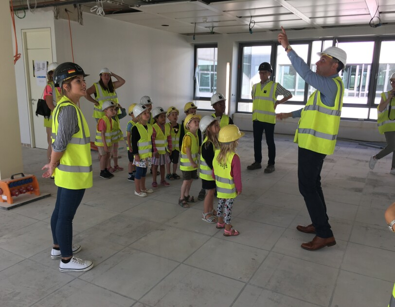 Children wearing vests and helmets at the tour of Amazon EU HQ in Luxembourg