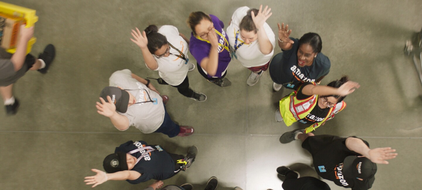 Overhead shot of people standing in a circle. They each have one hand raised.