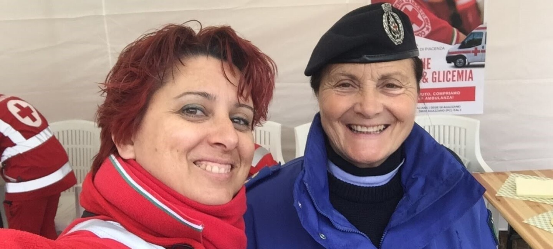 Due volontarie della croce rossa si scattano un selfie. La donna a sinistra è vestita di rosso e regge il telefono mentre scatta la foto, la donna a destra è vestita di blu e indossa un basco.