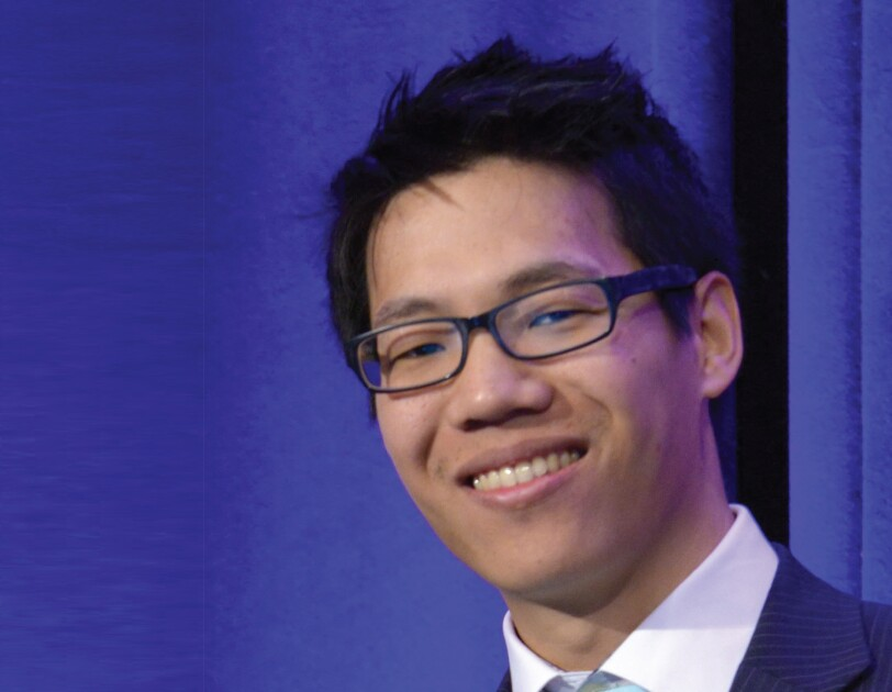 Headshot of William Lau in front of a blue curtain.
