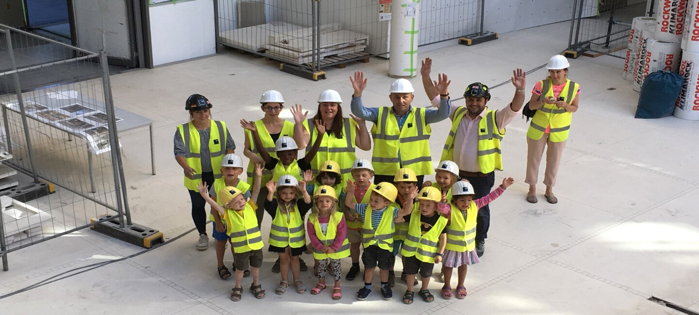 Pupils between age 4 and 6 wave at the camera with Amazonians and their teachers, all wearing neon yellow working vests and construction helmets.  They are at the construction site of Amazon's new headquarters building in Luxembourg.