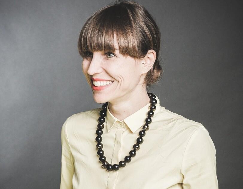 Eine Frau mit gelber Bluse und einem Zopf lächelt in die Kamera.