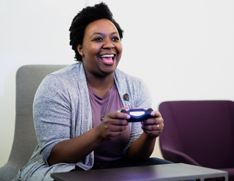 A seated woman holds a video game controller.