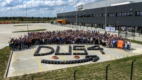 Ein Gruppenbild mit Mitarbeitern vor dem Amazon Gebäude. Vor ihnen wurde aus schwarzen Transportkisten der Schriftzug DUS4 geformt, zusammen mit dem Amazon Logo Pfeil und 2 orangenen Transportrobotern.