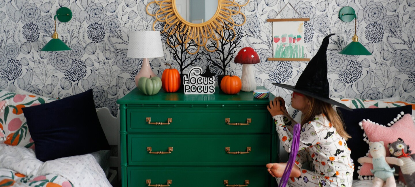 A little girl looks at an Echo Dot Kids' edition device on her nightstand while wearing a witch hat. The room is adorned in Halloween decorations.
