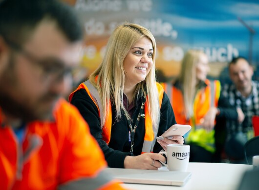 An Amazon employee drinks a coffee in the canteen