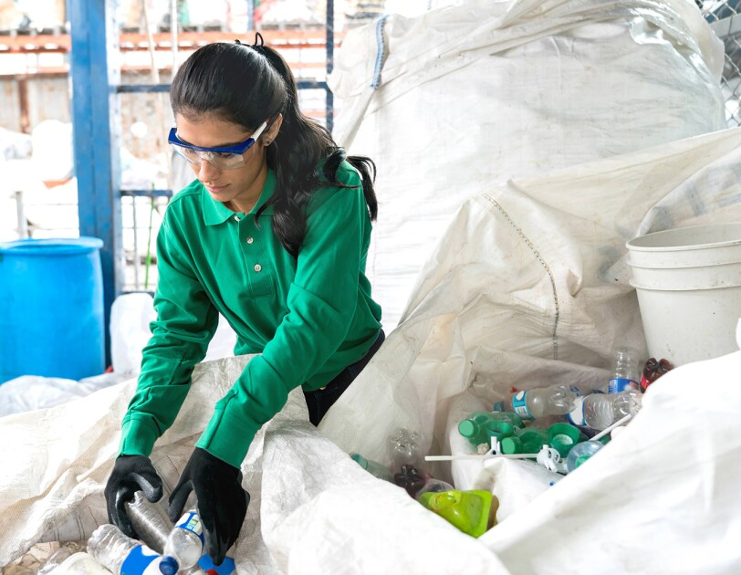 A woman wearing rubber gloves and safety goggles sorts through recyclable products