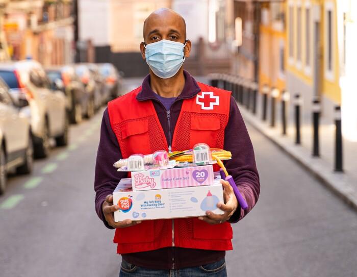 Alejandro Igor, voluntario de Cruz Roja. En una calle de Madrid. Él se encuentra en el inicio de la calle que hace cuesta. En un lado, desenfocados, coches aparcados y en el otro, también desenfocada, la acera. Él se encuentra en la mitad de la calle. Es moreno, lleva mascarilla azul y el pelo al cero. Vestimenta: con jeans de color azul, camiseta morada, polar morado y el chaleco de color rojo de la Cruz Roja. Mira a cámara y agarra con las dos manos dos cajas de cartón que són juguetes y encima también se puede apreciar algunos juguetes empaquetados en plástico,