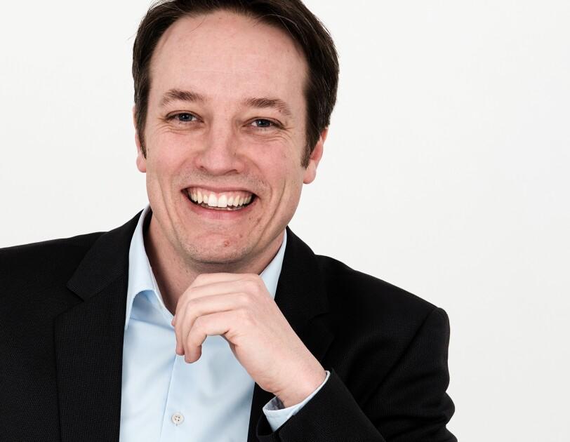Porträt von Tom Däxl im schwarzen Anzug und weißem Hemd