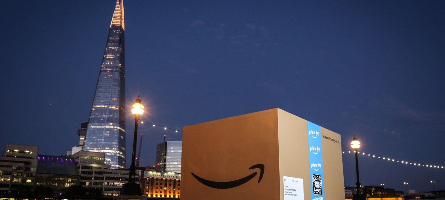 A giant Amazon box (about 8ft by 8ft) at dusk in London with the Shard in the background