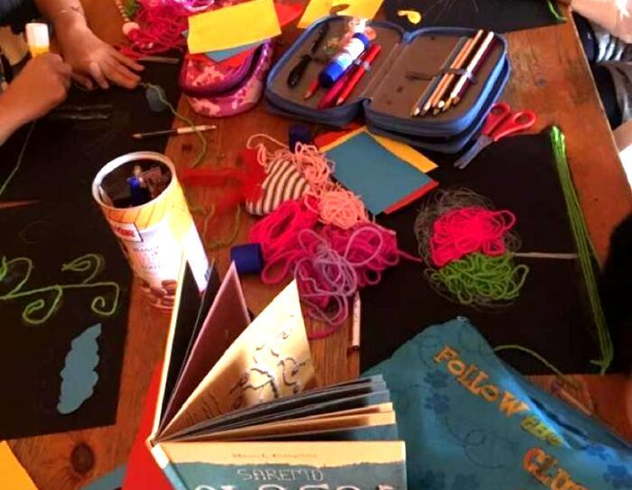 Primo piano di un tavolo su cui sono poggiati astucci, libri, matasse di cotone e colori. Sui lati si intravedono le mani di alcuni bambini che stanno colorando su degli album da disegno.