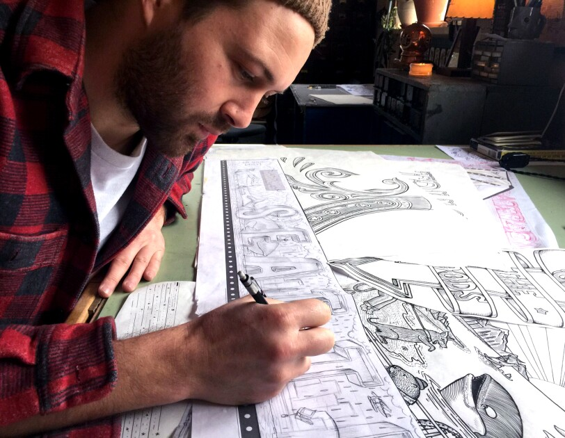 Kyler Martz in his Seattle studio, drawing the word Seattle onto a piece of sketch paper. He is wearing a red and black checked flannel shirt.