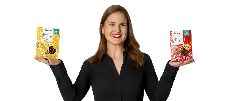 Eine Frau mit schwarzer Bluse lächelt in die Kamera. In ihren Händen hält sie Nudelpackungen.