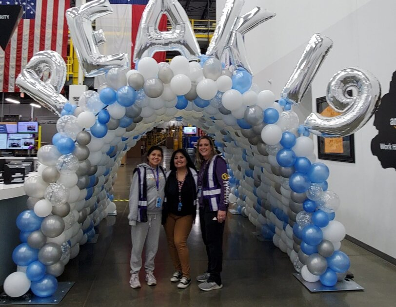 "Three Amazon associates stand under a balloon bridge with ""PEAK 19"" balloons displayed on the top."