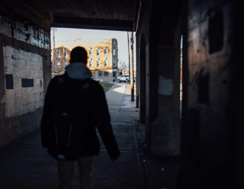 A shadowed figure shown from behind walks through a tunnel.