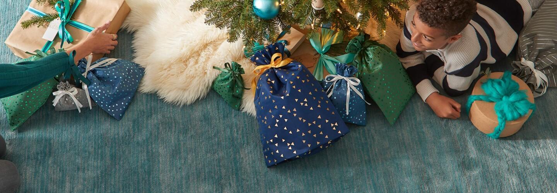 En los pies del árbol de Navidad se encuentra un niño de rodillas y lleno de bolsas de regalo de Amazon. En el suelo hay una alfombra de color verde-azul.  En el lado derecho está un niño moreno con un jersey de lana a rayas negras y blancas.  Al lado izquierdo se ve un brazo de una personas más mayor con un jersey verde. El árbol tiene un protector de color blanco y los paquetes de regalos son azules y verdes con motivos dorados.