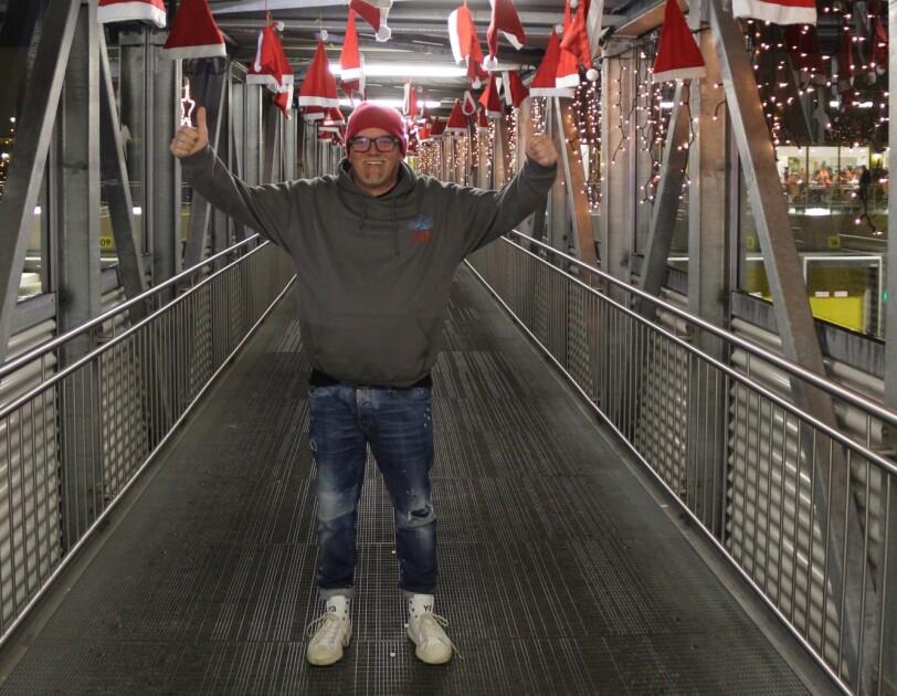 DJ Ötzi ist auf einem Gang zu sehen, über ihm hängen zahlreiche Weihnachtsmützen