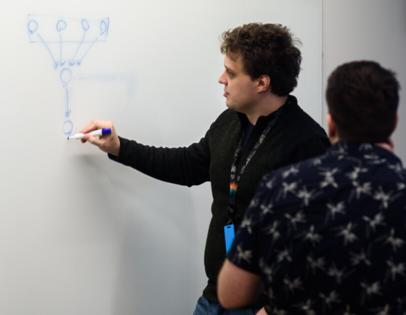 A man draws a diagram on a whiteboard while another man looks on.