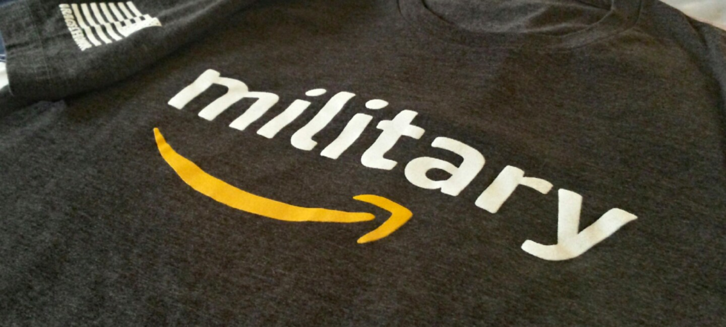 "A t-shirt with ""military"" and the Amazon logo lies on an American flag."