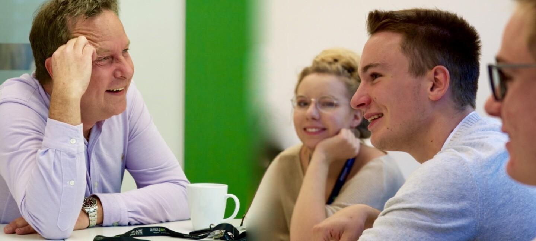 Ralf Kleber (links) im Gespräch mit 3 Jugendlichen: einem Mädchen und zwei Jungen