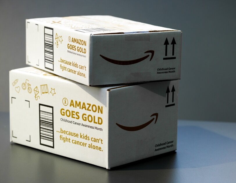 "Two Amazon boxes bearing the words ""Amazon Goes Gold"" and ""because kids can't fight cancer alone."""