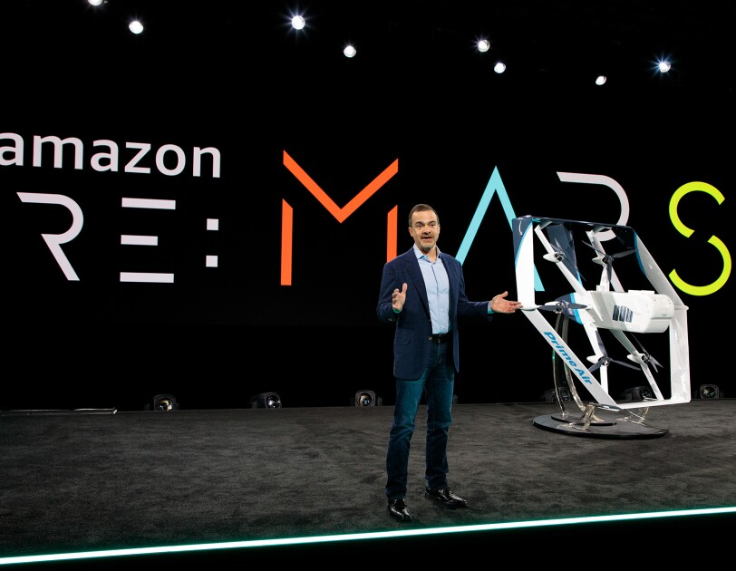 Jeff Wilke, CEO consumer worldwide at Amazon, stands on a stage. Behind him is a re:MARS logo. To his left is a drone painted in white and light blue.