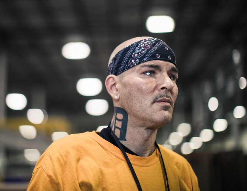 A man wearing a bandana photographed in a large warehouse space.