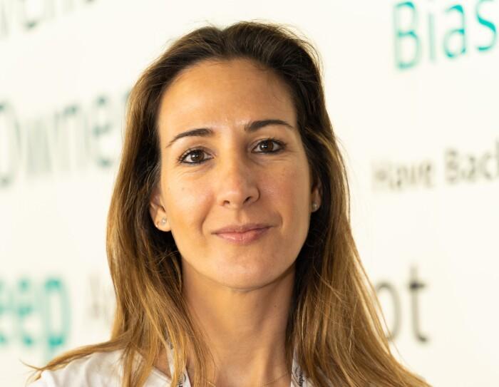 Silvia Cubero, 3P Program Manager, Marketplace Recruit and Dev. mirando a cámara y con el ordenador en las manos. Con una camisa blanca, dos collares, pendientes y el pelo por debajo del hombro.