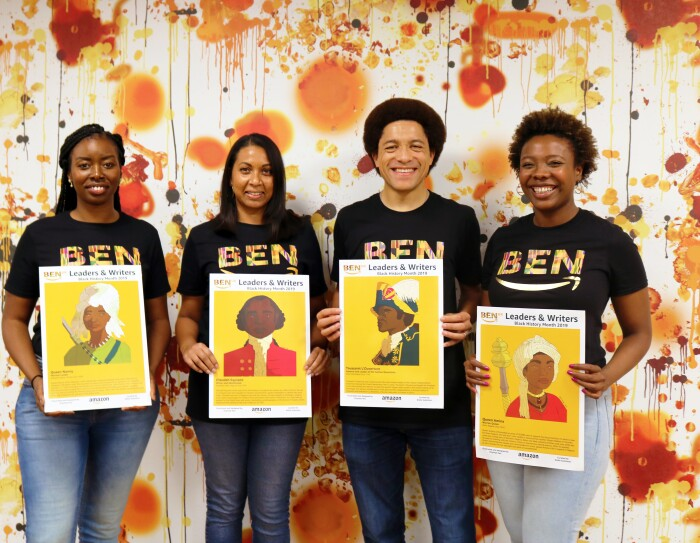 Orange and white group shot of employees holding artwork for BEN