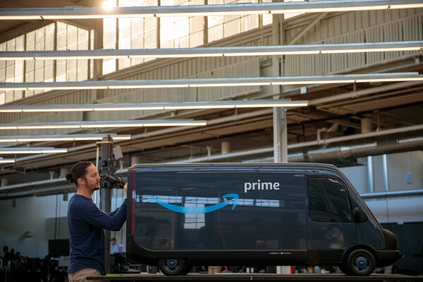 A man works on the back of a scale model of an Amazon electric delivery vehicle.