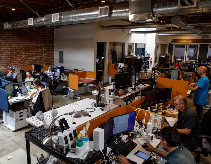 Employees sit at long tables with computers at Ring headquarters in Santa Monica, CA. The walls are brick.