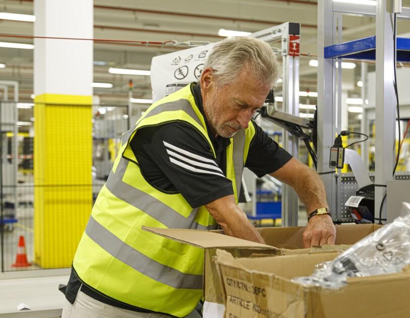 Ein Herr mit grauen Haaren und Sicherheitsweste beim Packen