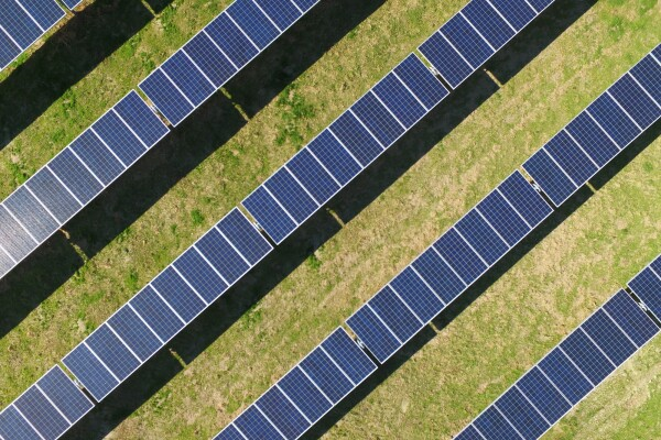 A birds-eye view of a field of solar panels, arranged diagonally