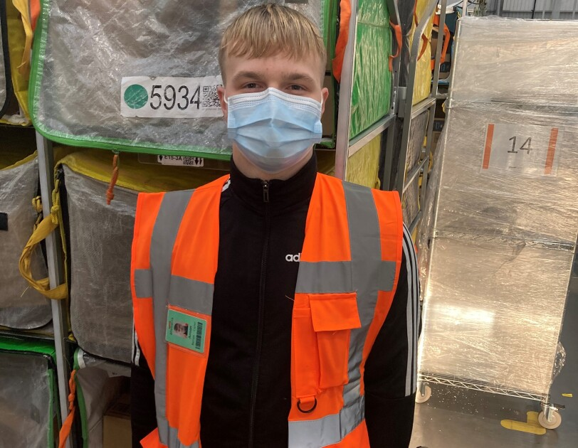 Anson Barratt – Carter, Sortation Associate at Amazon's delivery station in Sheffield, pictured wearing a high visibility vest and a face mask.