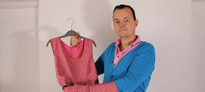 IUn homme tient dans ses mains une robe rose Oxalla sur un cintre