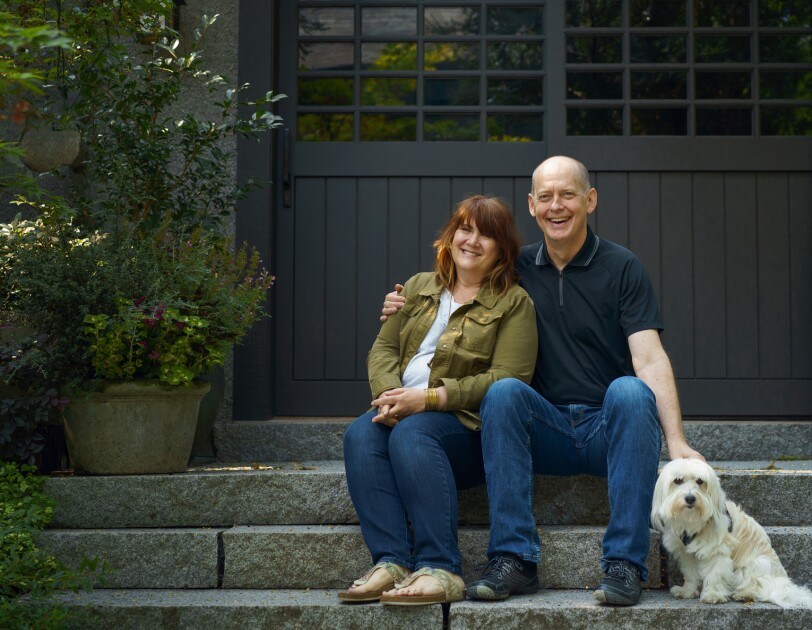 A woman and a man site with a dog on stone steps. They are smiling into the camera. She is wearing blue jeans and a green shirt. He is wearing blue jeans and blue shirt.
