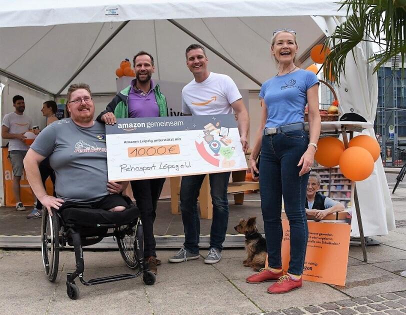 Vier Personen halten einen Spendenscheck. Links im Bild ist Marco Pratsch im Rollstuhl zu sehen