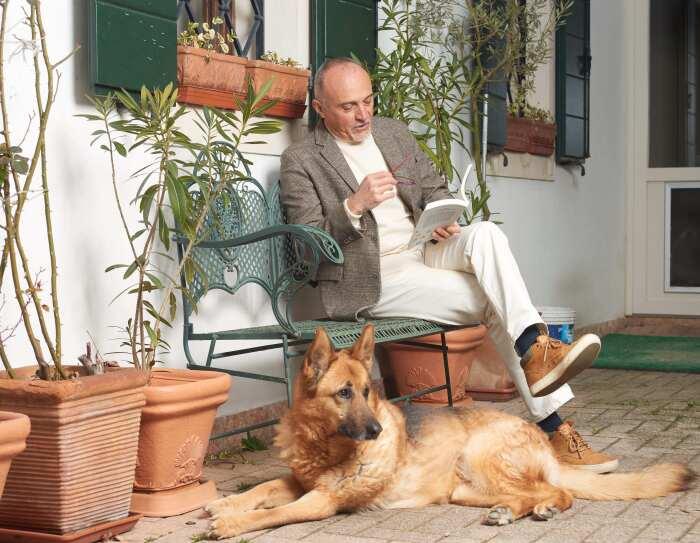 Lo scrittore Federico Maria Rivalta legge un libro sul portico di casa con un pastore tedesco ai suoi piedi.